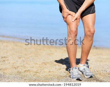 Muscle injury. Runner man with sprain thigh muscle. Athlete in sports shorts clutching his thigh muscles after pulling or straining them while jogging on the beach wearing running shoes. - stock photo