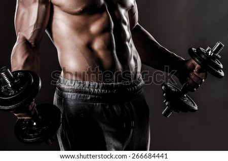 Muscle male body with weights - stock photo