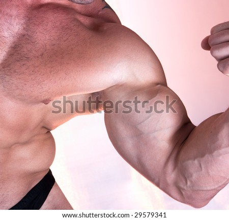 Muscle man biceps isolated on pink background - stock photo