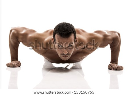 Muscle man dmaking push ups in studio, isolated over a white background - stock photo