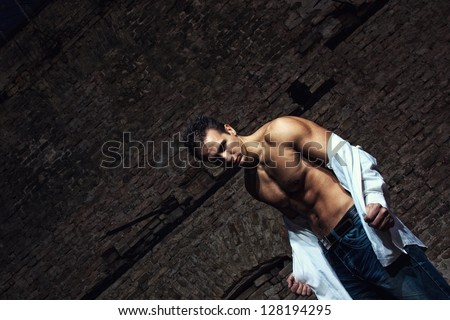 Muscle man in jeans and white shirt at abandoned factory - stock photo