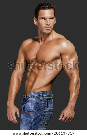 Muscle man posing in studio, isolated over a gray background - stock photo