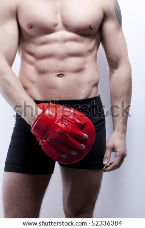 Muscle man's body in gym, with boxing glove - stock photo