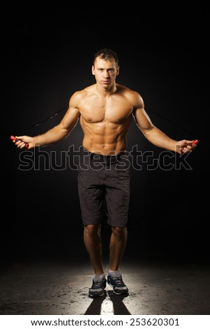muscle man skipping rope on black background  - stock photo