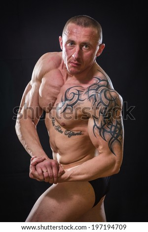 Muscle man with tattoos - stock photo