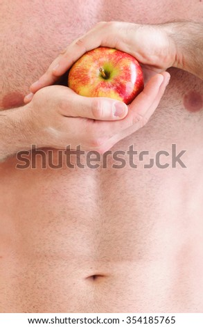 Muscle sexy wet naked young man torso and red apple in hands diet - stock photo