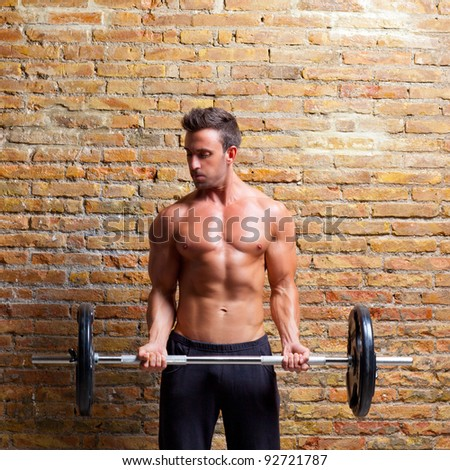 muscle shaped body man with weights on brick wall gym - stock photo