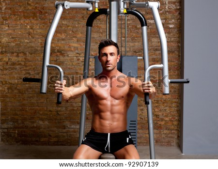 muscle shaped man exercise on sport gym fitness club in brick wall