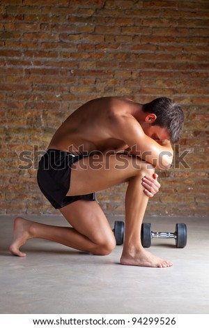 muscle shaped man on knee thinking with thinker posture - stock photo