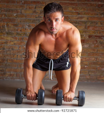 muscle shaped man on knees with training weights on brick wall - stock photo
