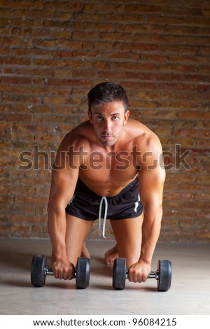 muscle shaped man on knees with training weights on brickwall - stock photo