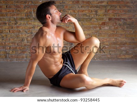 muscle shaped man sitting relaxed on grunge brick wall