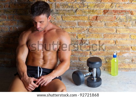 muscle shaped man tired sitting relaxed with weights and energy drink