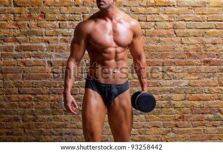 muscle shaped underwear man with weight on gym brick wall - stock photo