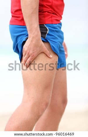 Muscle sports injury. Running muscle strain injury in thigh. Closeup of runner touching leg in muscle pain. - stock photo