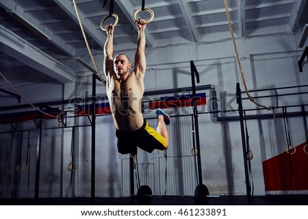 Muscle-up exercise young man doing intense cross fit workout at the gym on gymnastic rings