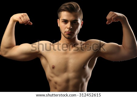 Muscle young man on dark background - stock photo