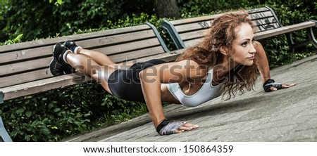 Muscled fitness girl is working out in the park near the bench - stock photo