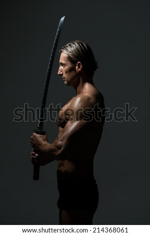 Muscled Male Model In Studio With A Sword - Portrait Of A Handsome Muscular Ancient Warrior With A Sword - stock photo