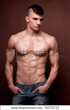 Muscled male model posing in jeans - stock photo