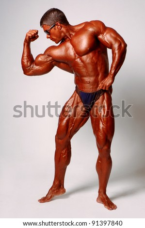 Muscled male model posing in studio on a light background - stock photo
