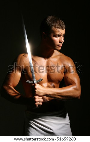 Muscled male model posing in studio with a sword - stock photo