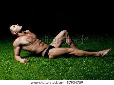 Muscled male model posing on the grass - stock photo