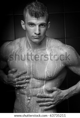 Muscled male model with milk drops on his torso - stock photo