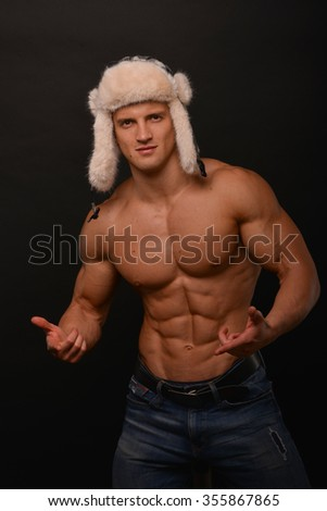Muscled male posing in winter hat