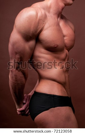 Muscled male torso on brown background - stock photo
