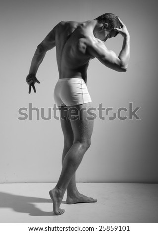 Muscled model in studio in black and white
