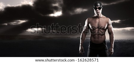 Muscled swimmer man with cap and glasses outdoor at rough sea with stormy dark sky. Extreme fitness sport.