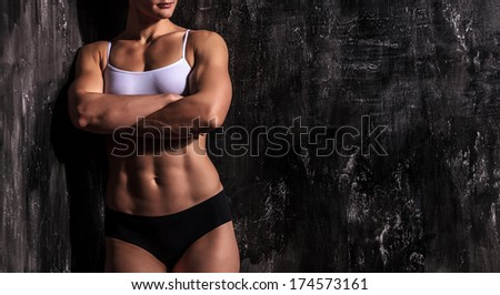 Muscled woman against a grunge background - stock photo