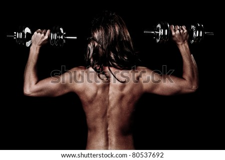 Muscles of a Woman's Back and Arms Lifting Weights - stock photo