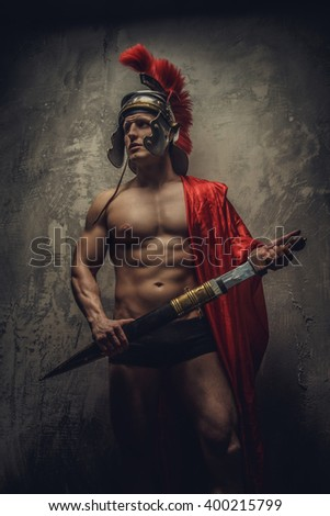 Muscualr man in a Roman clothes with sword.