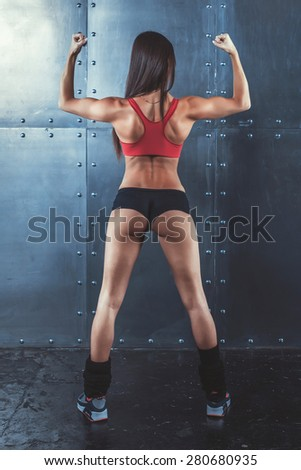 Muscular active athletic young woman showing muscles of the back shoulders and hands fitness, sport, training and lifestyle concept - stock photo