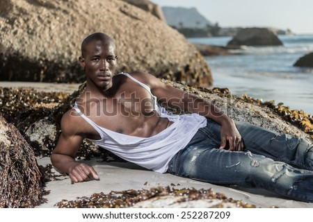 Muscular African american black male model, ripping his white vest shirt on the beach with great power and anger