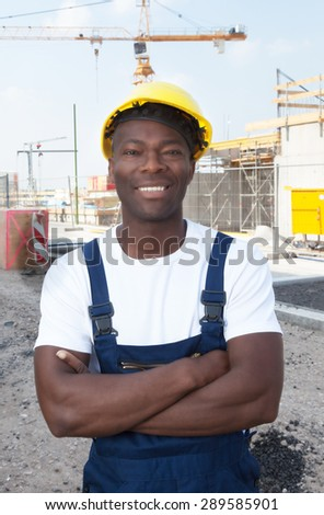 Muscular african american construction worker at building site - stock photo