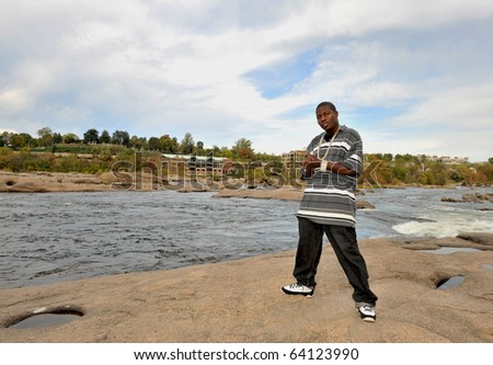 Muscular African american man wearing chains standing on the rocks of a river. - stock photo