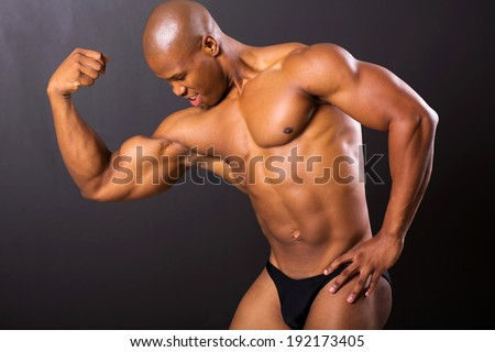 muscular african man posing on black background - stock photo