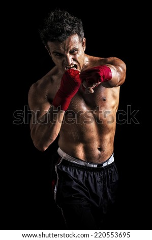 Muscular Aggressive Man Showing His Fist isolated on black background - stock photo