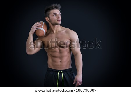 Muscular american football player standing with ball in hand, on dark background - stock photo