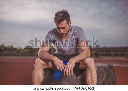 Muscular and fit man resting after training and drink water.