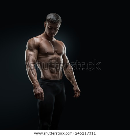 Muscular and fit young bodybuilder fitness male model posing over black background. Dramatic light. - stock photo