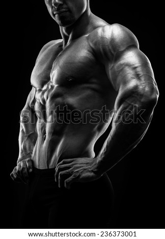 Muscular and fit young bodybuilder fitness male model posing over black background. Studio shot on black background. Black and white photo - stock photo