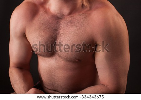 Muscular and fit young man bodybuilder fitness male model posing over black background