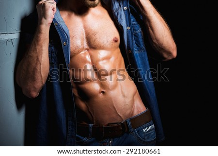 Muscular and sexy body of young sport man in jeans shirt with perfect abs and chest - stock photo