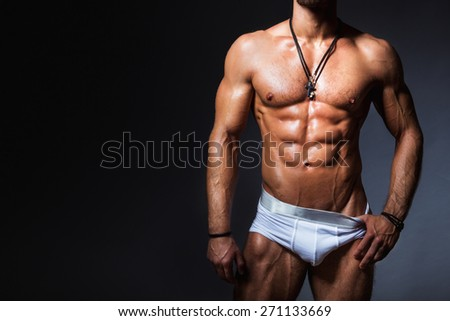 Muscular and sexy torso of young man with perfect abs in panties