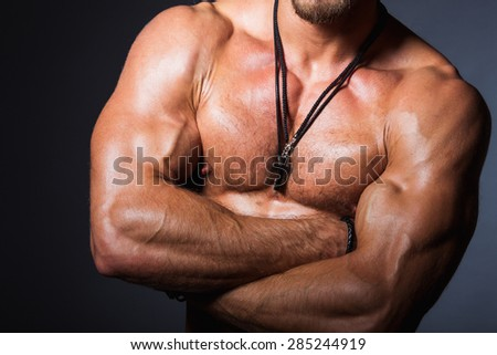 Muscular and sexy torso of young sporty man showing his perfect bicep and body. Torso part. Front view - stock photo