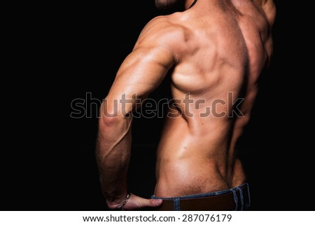 Muscular and sexy torso of young sporty man showing his perfect body, triceps and back muscles - stock photo